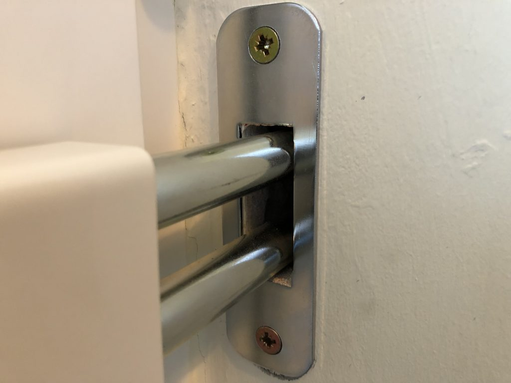 Hevederzár pántja masszívan a falban, ezt az ajtót már nem törik be