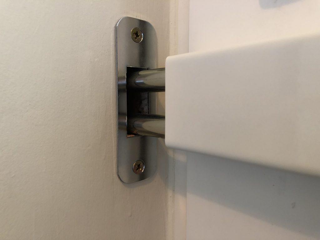 Hevederzár pántja egy külső fém keretbe igazodik, így van megerősítve a fal törését megakadályozva